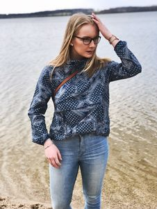 Free Woman In Blue And Gray Long-sleeved Shirt And Blue Denim Jeans Near Body Of Water Stock Images - 115628404