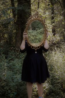 Free Woman Holding Mirror Against Her Head In The Middle Of Forest Royalty Free Stock Image - 115628416