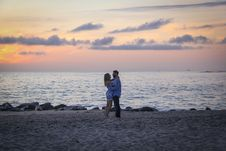 Free Couple Face To Face Stands On Seashore Near Calm Water During Golden Hour Stock Photos - 115694053