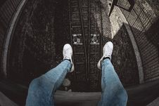Free Person In Blue Denim Stonewashed Fitted Jeans And White Low-top Sneakers Stock Photos - 115694253