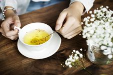 Free Person Holding Silver Spoon On White Ceramic Teacup With Yellow Liquid Inside Stock Images - 115773804
