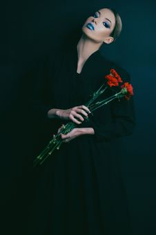 Free Woman In Black Long-sleeved Dress Holding Red Flowers Royalty Free Stock Photography - 115773807
