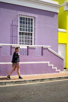 Free Woman Walking Near Purple Painted Building Stock Images - 115843994