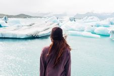 Free Woman Wearing Purple Shirt Overlooking At Body Of Water And Snow Covered Field Stock Photo - 115844220