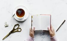 Free Person Holding Empty Book Near Pen And Shears With A Cup Of Tea Royalty Free Stock Photo - 115913685