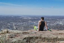 Free Man Wearing Black Tank Top Sitting Near Edge Of Cliff Stock Photography - 115913842