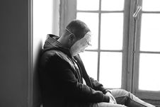Free Man Wearing Mask Sitting Near Window Panel Royalty Free Stock Photo - 115976865