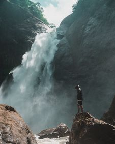 Free Man Standing On Brown Rock Cliff In Front Of Waterfalls Photography Stock Image - 115976931