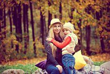 Free Woman Wearing Purple Long-sleeved Shirt Hugging Girl Wearing White Jacket Near Trees At Daytime Stock Photos - 115976993