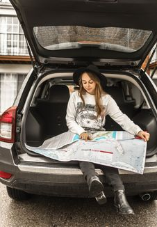 Free Woman Using Map On Gray Car Compartment Royalty Free Stock Photography - 115977177