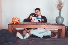 Free Couple Reading Book Sitting On Front Of Rectangular Brown Wooden Coffee Table Stock Photo - 116049890