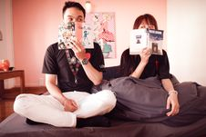 Free Couple Holding Books Sitting On Bed Royalty Free Stock Photography - 116049917