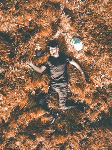 Free Man In Black Crew-neck Shirt And Black Pants Laying In Brown Dry Leaf Royalty Free Stock Image - 116049996