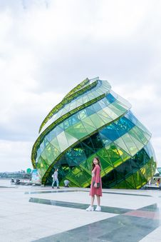 Free Woman In Red Dress Standing In Front Of Green Glass Elliptical Building Stock Photos - 116050003