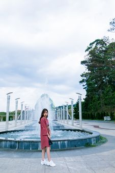Free Woman In Red Long-sleeved Dress Standing Near Water Fountain At Daytime Royalty Free Stock Photography - 116050007