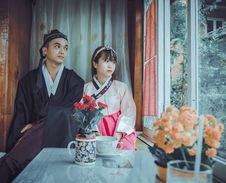 Free Couple Wearing Korean Traditional Dress Near Windowpane Staring At The Window Stock Photo - 116050020