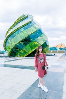 Free Woman In Red Long-sleeved Top Wearing White Sneakers Walking In Front Of Green And Blue Glass Building Stock Photo - 116050040