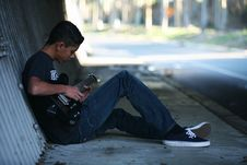 Free Man Sitting Near Wall Playing Guitar Stock Images - 116147304
