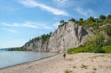 Free Woman Walks On Brown Seashore Near Cliff With Green Trees Under Blue And White Sky Royalty Free Stock Photography - 116147347