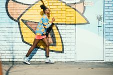 Free Woman Wearing Blue And Yellow Long-sleeved Shirt Walking Near White And Yellow Painted Wall Royalty Free Stock Image - 116147396