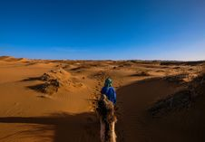 Free Man Wearing Blue Jacket Riding Camel Walking On Desert Royalty Free Stock Photo - 116147495