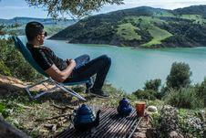 Free Man Sitting Overlooking Lake Stock Image - 116147551