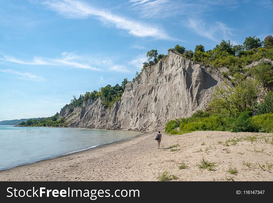 Woman Walks on Brown Seashore Near Cliff With Green Trees Under Blue and White Sky