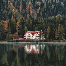 Free White And Orange House Beside Forest And Body Of Water Stock Photo - 116232110