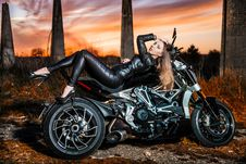 Free Woman Wearing Black Jacket And Pants Leaning On Touring Motorcycle Stock Photos - 116232153