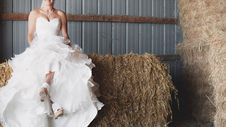Free Woman In White Strapless Sweetheart Neckline Bridal Gown Sitting Of Brown Hay Royalty Free Stock Images - 116232179