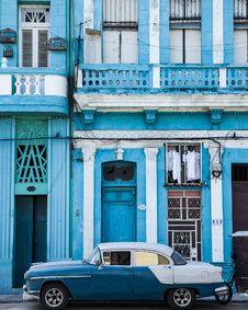 Free Classic Blue And White Sedan Near Building Stock Image - 116371131