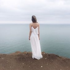 Free Woman In White Spaghetti Strap Dress Standing On Cliff Stock Photography - 116371182