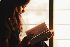 Free Woman Reading A Book Beside The Window Stock Photo - 116371190