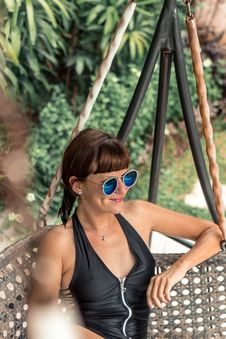 Free Woman Wearing Sunglasses Sitting On Swing Stock Photos - 116371483