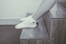 Free Person Wearing Pair Of Foot Socks Sitting On Staircase Stock Photos - 116371613