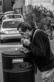 Free Grayscale Photography Of Man Leaning On Black Trash Bin Royalty Free Stock Images - 116371619