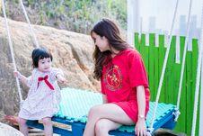 Free Woman Wearing Red Crew-neck Shirt Sitting On Swing Bench Stock Image - 116504471