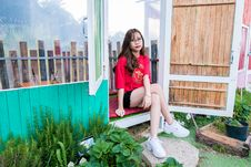 Free Woman In Red Shirt And Black Short Shorts Sitting On Wooden Floor Royalty Free Stock Image - 116504486