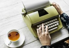 Free Person Holding Type Writer Beside Teacup And Saucer On Table Stock Image - 116504581
