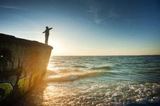 Free Silhouette Of Person On Cliff Beside Body Of Water During Golden Hour Royalty Free Stock Images - 116504679