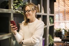 Free Selective Focus Photography Of Woman Using Smartphone Beside Bookshelf Royalty Free Stock Images - 116695129