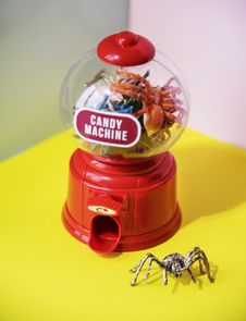 Free Red And Clear Plastic Candy Machine On Yellow Desk Stock Photos - 116695403