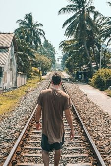 Free Man In Brown Shirt Standing On Train Rail Near Coconut Palms Stock Photography - 116696182