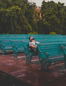 Free Man Sitting And Closing Eyes On Teal Bench Royalty Free Stock Image - 116776276