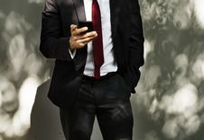 Free Man Wearing Black Tuxedo Holding Black Smartphone Stock Photography - 116853962