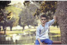 Free Man Sitting On Bench Beside Tree Royalty Free Stock Photos - 116854028