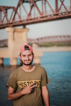 Free Man Wearing Gray Historic-printed T-shirt And Red Snapback Cap Taking Photo Beside Body Of Water Stock Image - 116854041