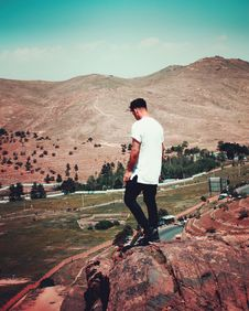 Free Man In White T-shirt And Black Pants Standing On Cliff Royalty Free Stock Image - 116854046