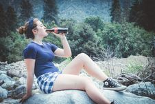Free Woman In Blue Shirt Sitting On Rock Drinking Coca-cola Stock Images - 116854264