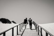 Free Grayscale Photography Of Man And Woman Crossing Bridge Royalty Free Stock Photography - 116854297
